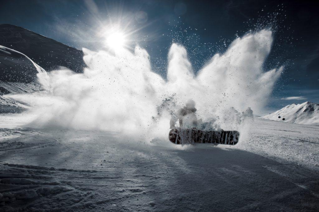 雪しぶきを上げるスノーボーダー