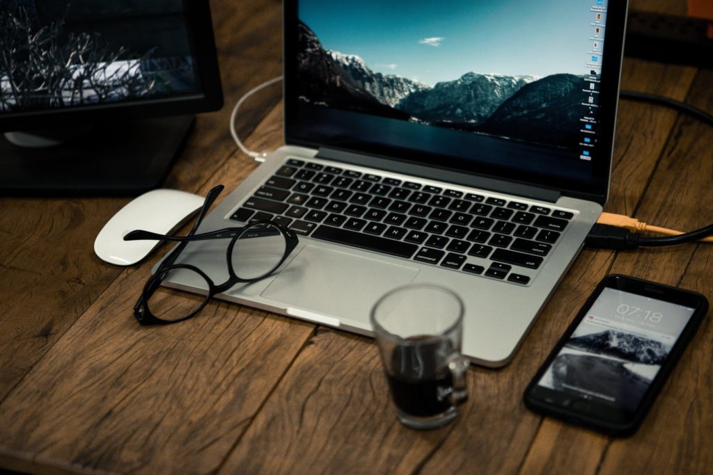 机の上にパソコンとスマートフォンが置いてある画像