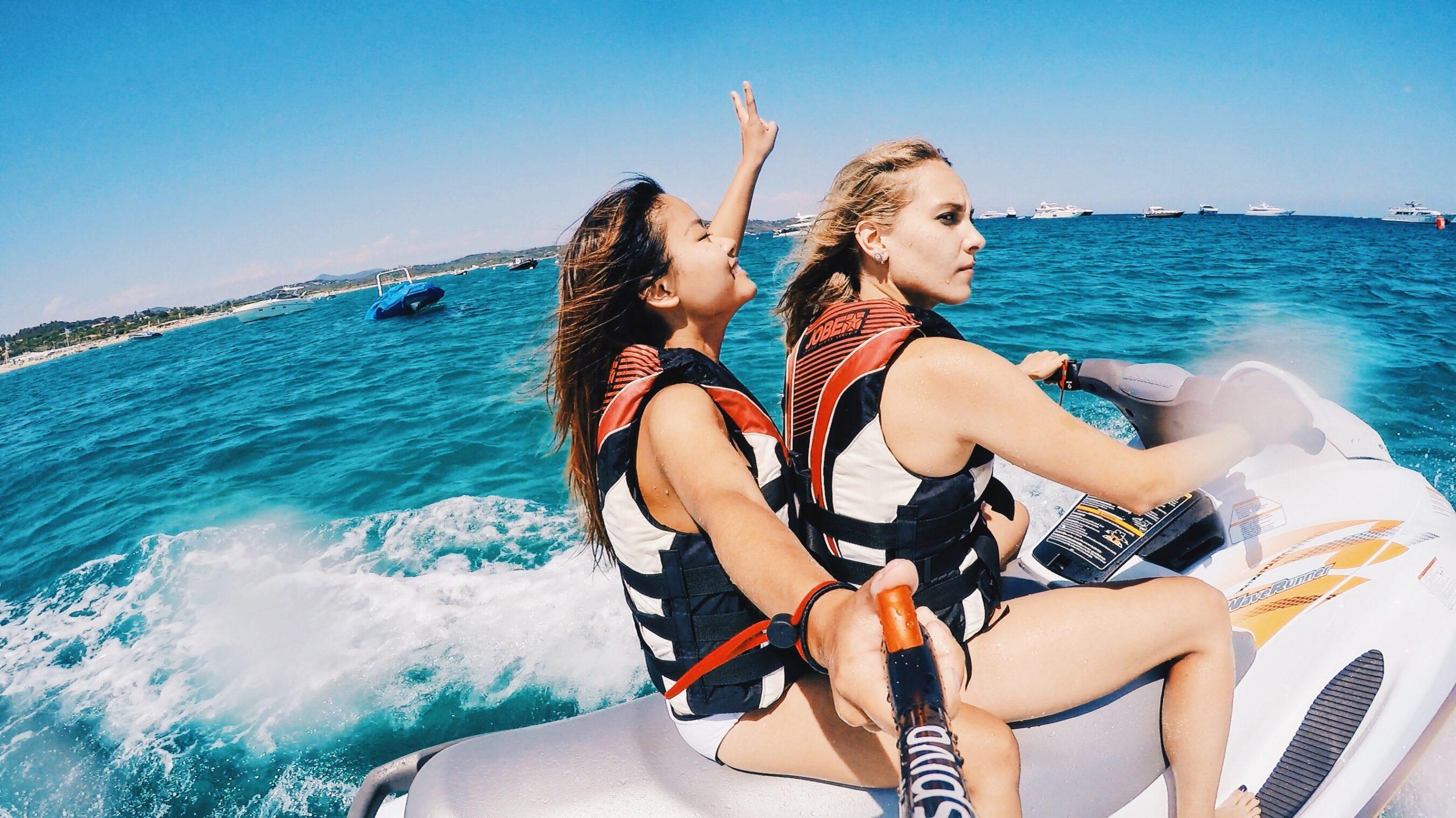 水上バイクに乗ってアクションカメラで撮影する女性